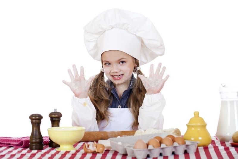 在厨房和展示手的逗人喜爱的小女孩烘烤 免版税库存照片