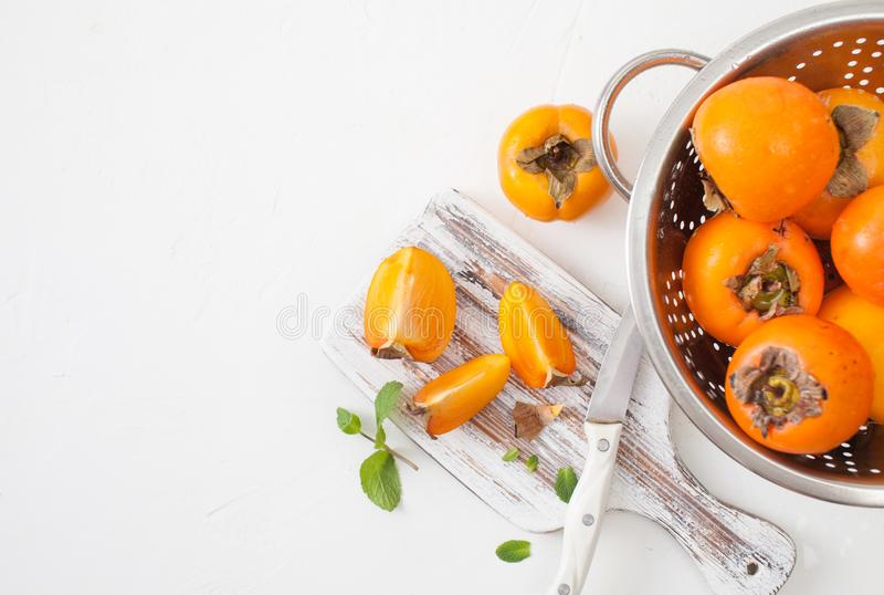 在厨房委员会的新鲜的成熟柿子在白色 图库摄影