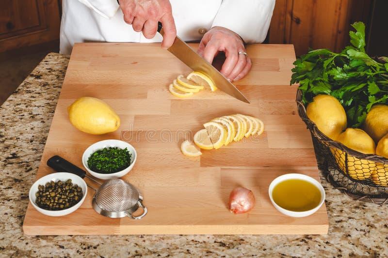 在厨房显示的切柠檬人的手 免版税库存图片
