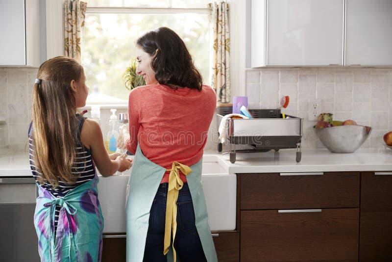 在厨房水槽的妈咪和女儿洗涤的手,后面看法 免版税库存照片