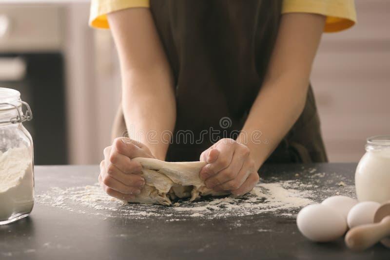 在厨房用桌上的妇女揉的面团 免版税库存照片
