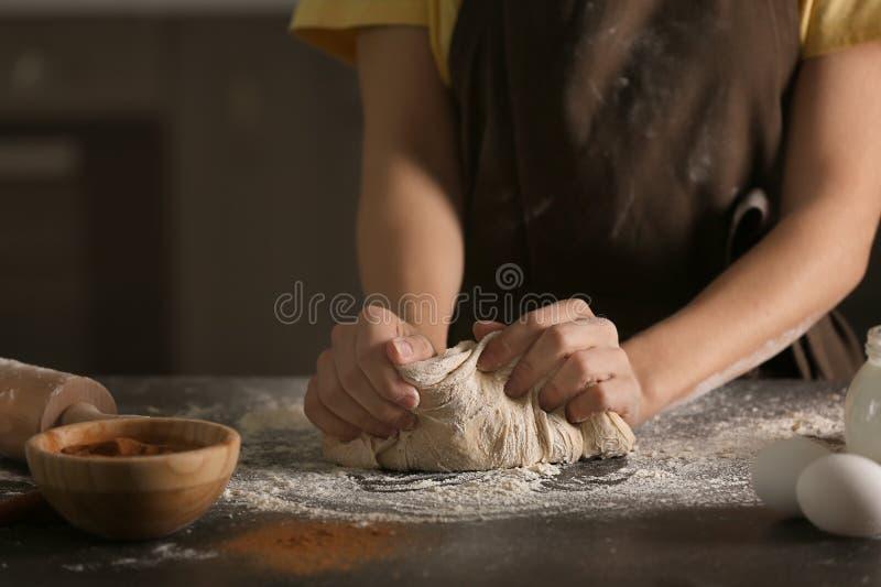 在厨房用桌上的妇女揉的面团 库存照片