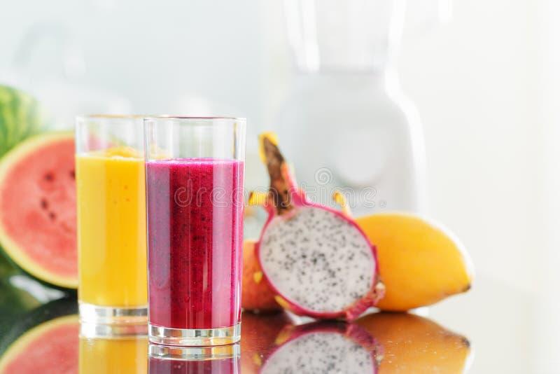 在厨房用桌上的新鲜水果圆滑的人 搅拌器在背景中 免版税库存照片