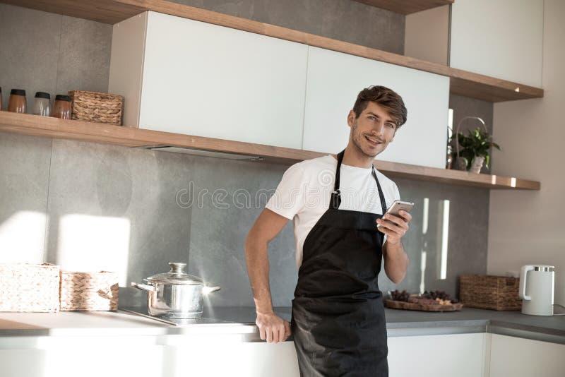 在厨房用桌附近的有吸引力的年轻人身分 免版税库存照片