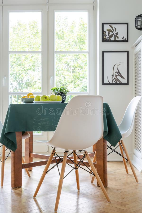 在厨房用桌,真正的照片旁边的时髦的白色椅子 免版税库存图片