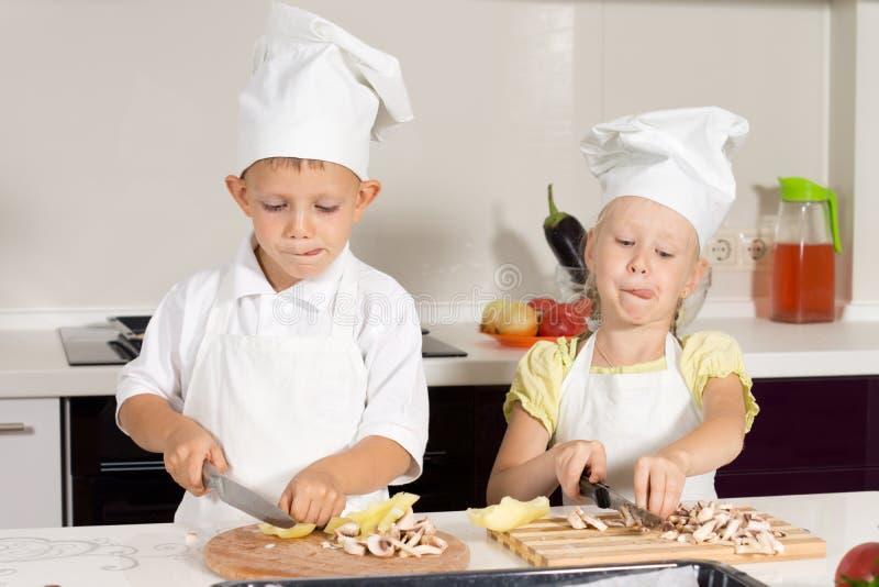 在厨房的孩子厨师繁忙的切的成份 库存图片