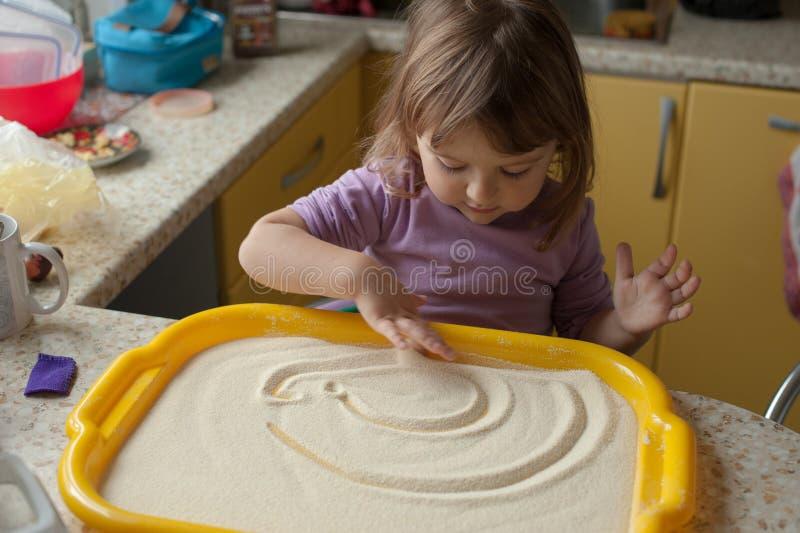 在厨房的小女孩绘画与手指的沙子的 免版税库存照片