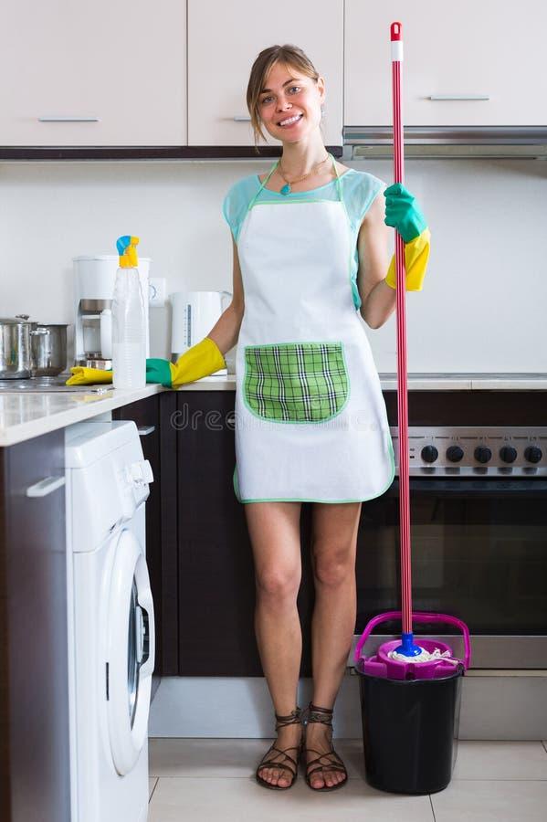 在厨房的快乐的佣人清洁 免版税图库摄影