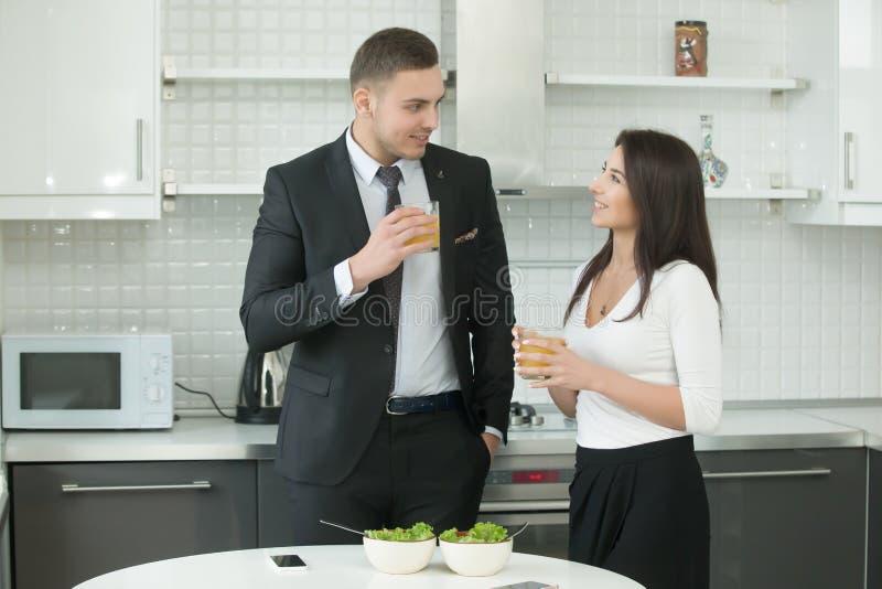 在厨房的男人和妇女饮用的汁液 库存照片