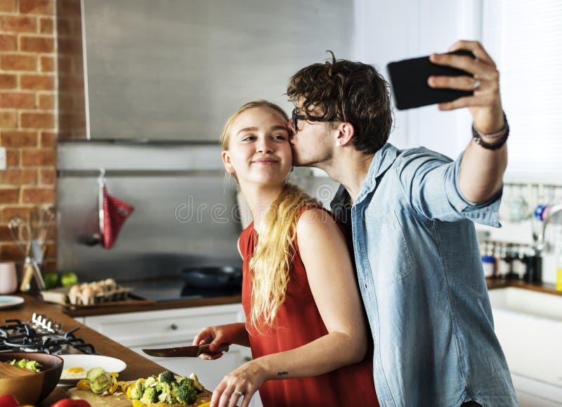 在厨房里供以人员采取与他的妻子的一selfie 免版税库存图片
