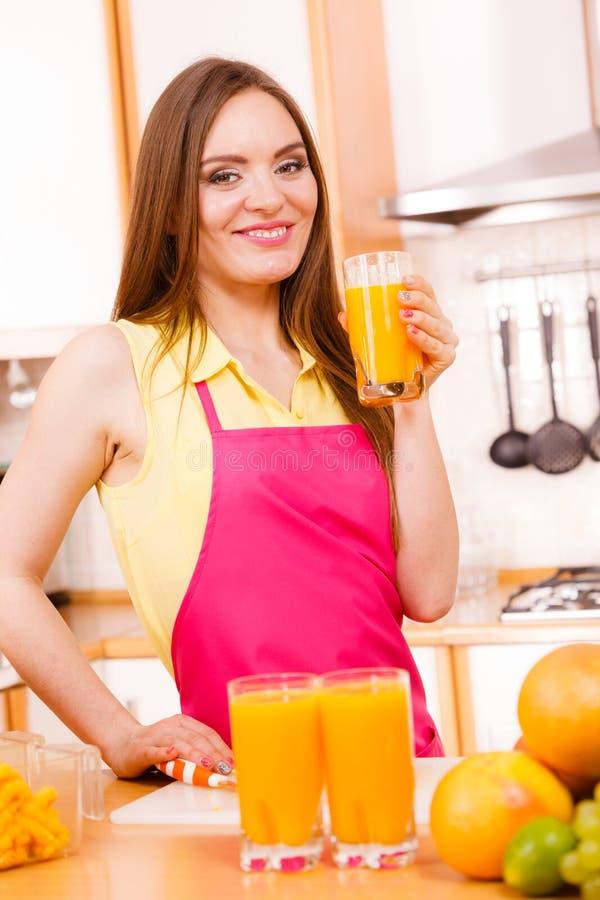 在厨房里喝新鲜的橙汁的妇女 免版税库存照片