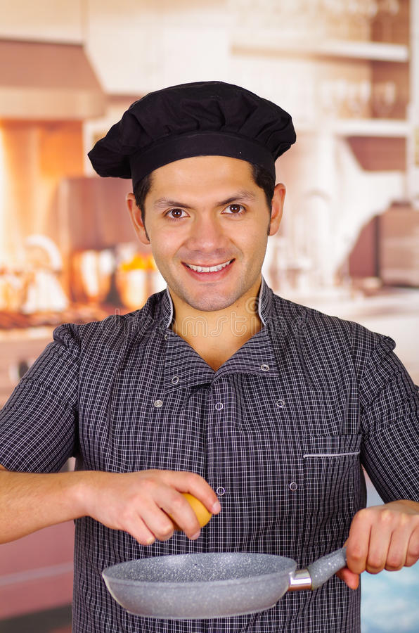 在厨房里在他的手上拿着一个平底锅用一个鸡蛋烹调盘, churrasco ecuatorian烹调的微笑的人 免版税图库摄影