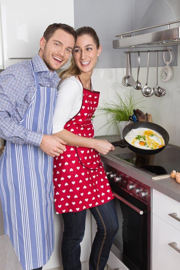 在厨房里烹调一起油煎的年轻新已婚夫妇 免版税图库摄影