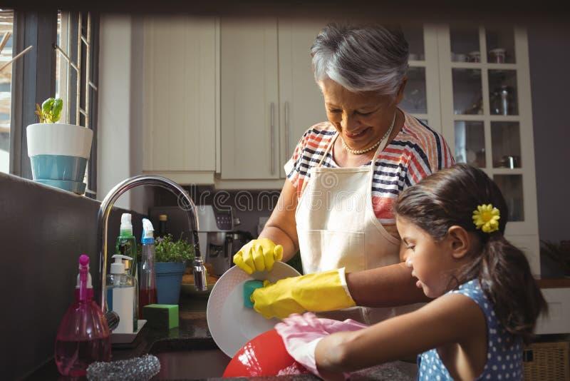 在厨房水槽的祖母和孙女洗涤的器物 库存图片