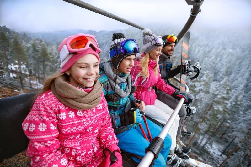 在去的滑雪电缆车的家庭滑雪地形 免版税库存照片