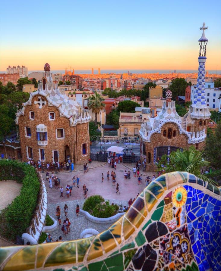 在参观公园Guell,巴塞罗那,西班牙的游人的日落 免版税图库摄影