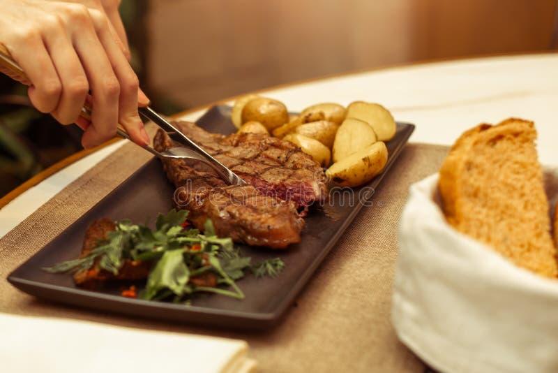 在叉子和刀子的肉的焦点 美好的女性手在桌面牛肉striploin牛排的一家餐馆 库存照片