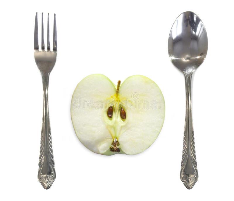 在叉子和匙子之间的苹果计算机 库存照片