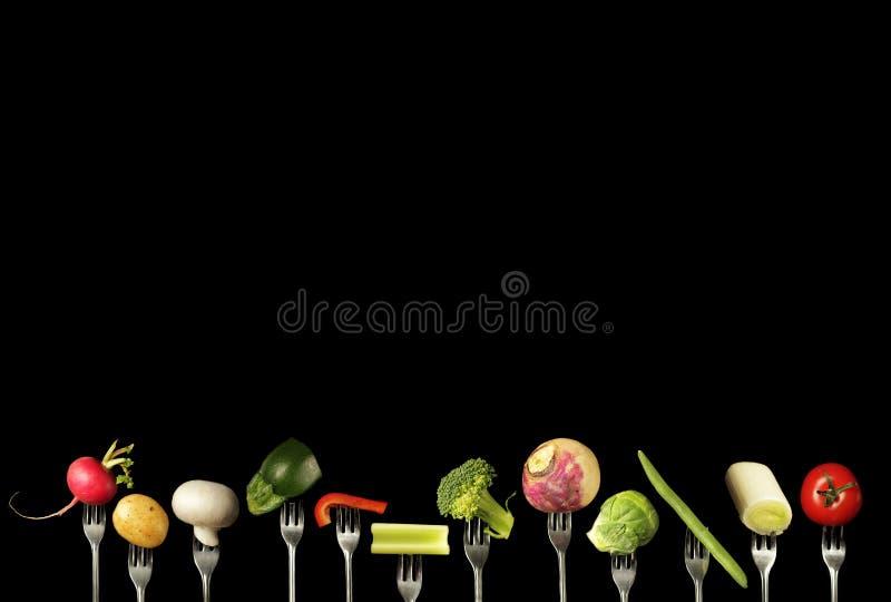 在叉子的菜在黑色 免版税库存图片