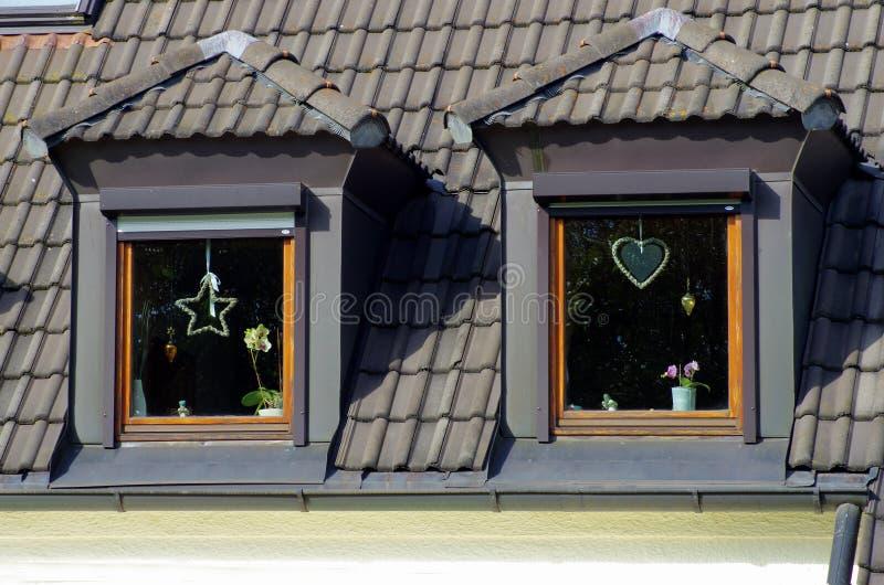 在双重斜坡的四边形屋顶的两个窗口 免版税图库摄影