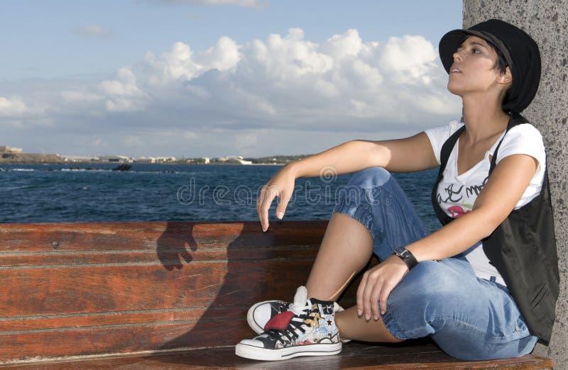 在反叛海运坐的妇女年轻人附近 库存照片