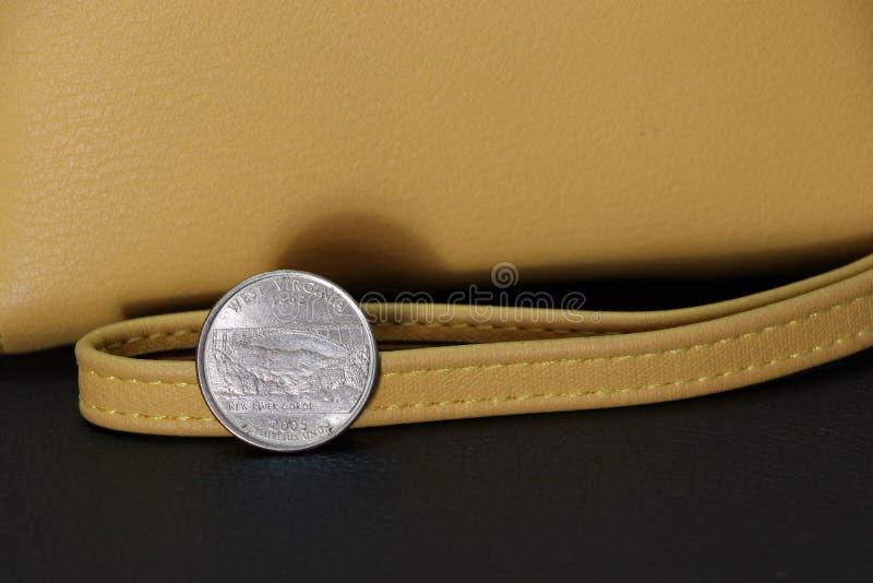 在反向USD的美元硬币四分之一与沙子在黑地板上的颜色钱包 免版税库存图片