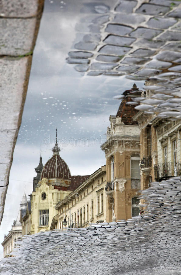 在反射在水坑的街道的大厦在雨以后 免版税库存照片