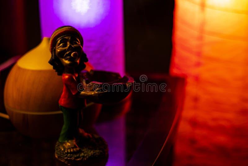 在反射性书桌上的巴布・马利小雕象 免版税库存图片