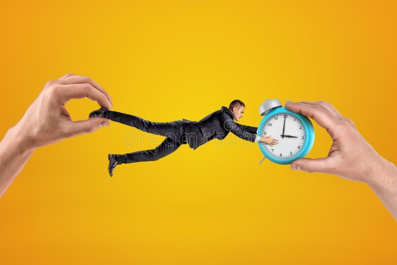 在反方向被拉扯的小商人由两个一臂之力和抓住用他的两只手在闹钟 免版税库存照片