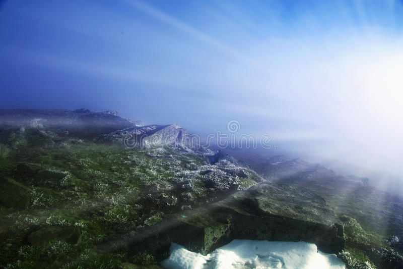 在发光在阳光下的山顶部的美丽如画的看法 免版税库存图片