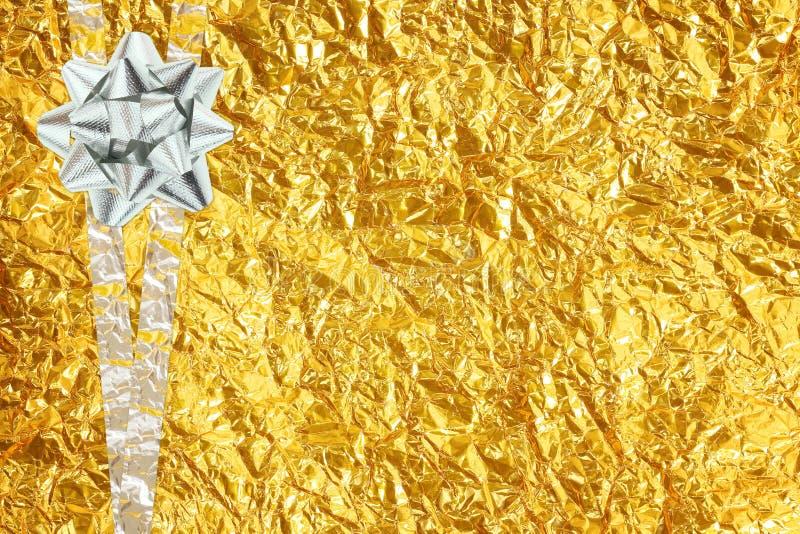 在发光的箔的发光的黄色叶子金和银丝带 免版税库存照片