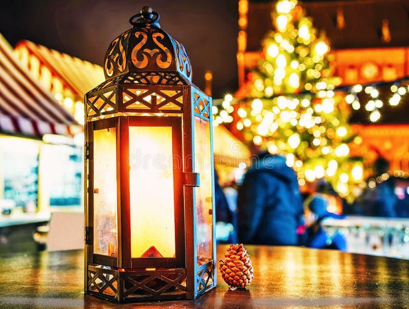 在发光的蜡烛灯笼的小锥体桌附近在圣诞节市场上在冬天里加在拉脱维亚 免版税图库摄影