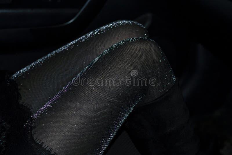 在发光的裤袜的诱人的苗条女性腿在黑暗 免版税库存图片
