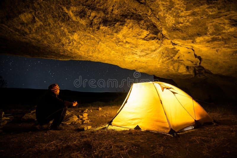 在发光的野营的帐篷附近的旅客在夜洞穴在满天星斗的天空下 免版税库存照片
