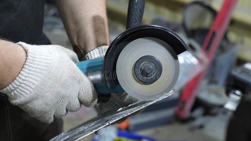 在发光的金属的工作者裁减在白色防护手套研磨机 特写镜头 库存照片