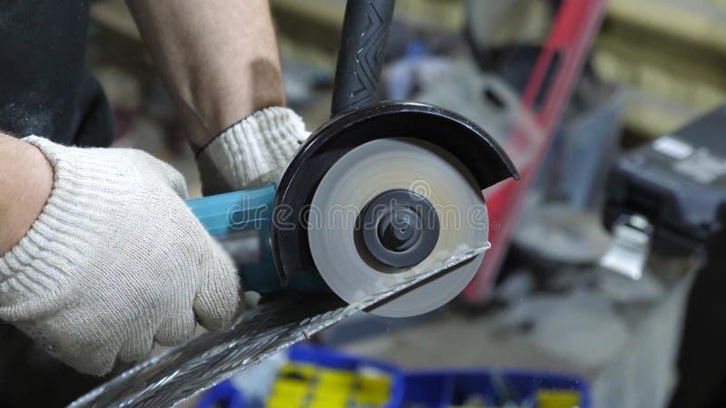 在发光的金属的工作者裁减在白色防护手套研磨机 特写镜头 免版税库存照片