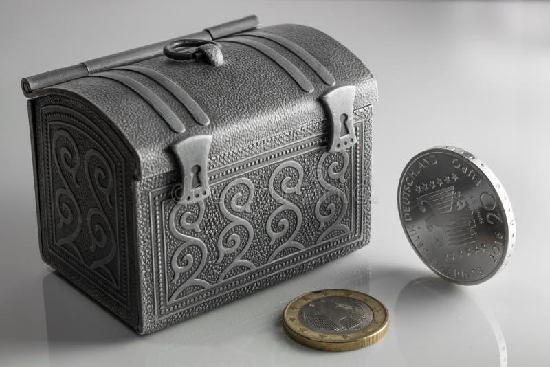 在发光的银色箱子的金钱在桌上 从不同的国家的欧洲硬币股票 库存图片