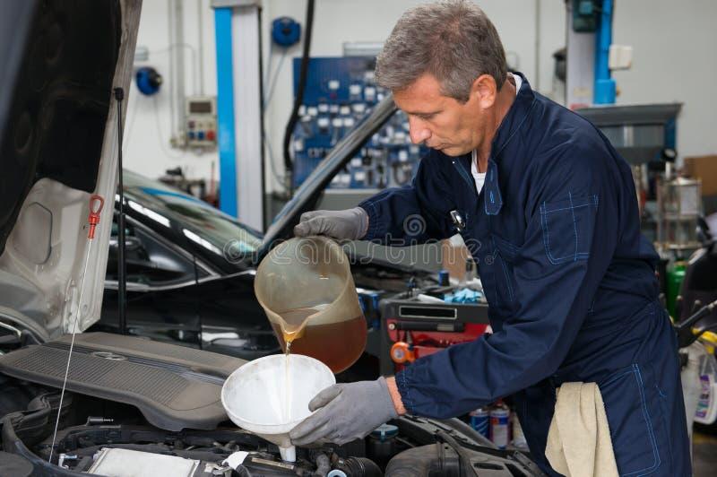 在发动机的技工倾吐的油 库存照片
