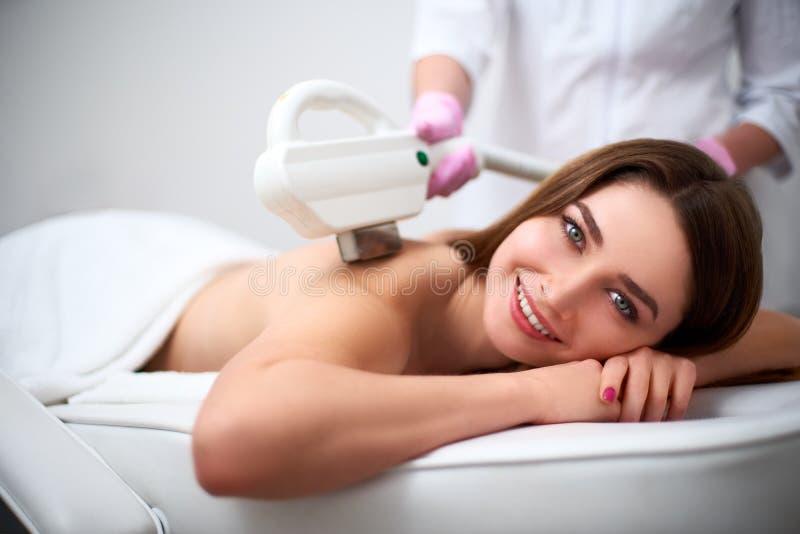 在发廊的年轻俏丽的微笑的妇女后面激光epilation 做与elos的美容师去壳治疗 库存照片