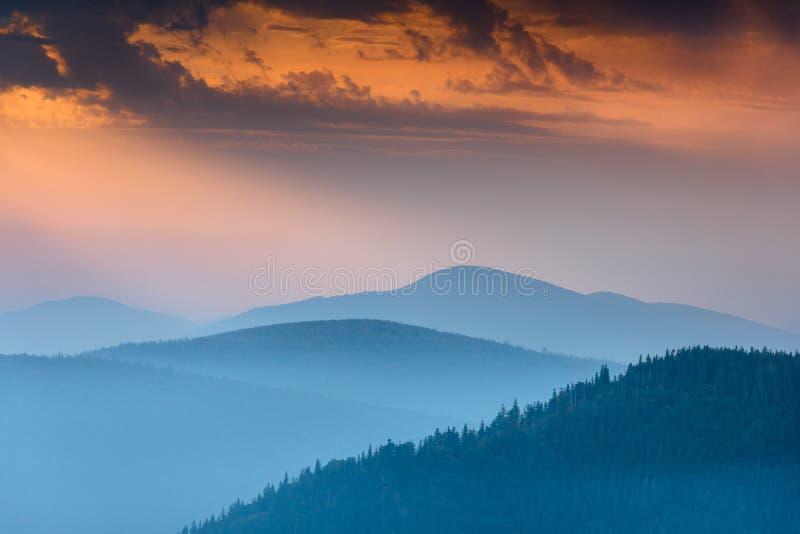 在发烟性山上峰顶的意想不到的日出有看法到有薄雾的小山里 免版税库存图片