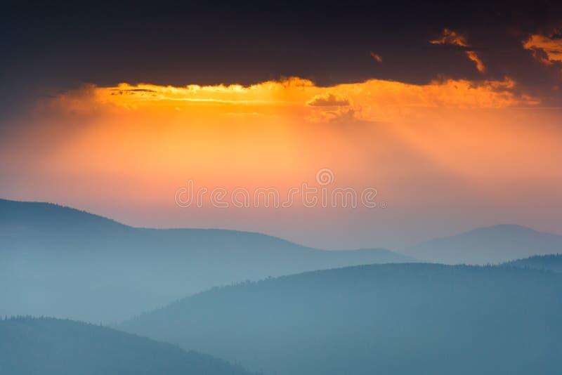 在发烟性山上峰顶的意想不到的日出有看法到有薄雾的小山里 图库摄影