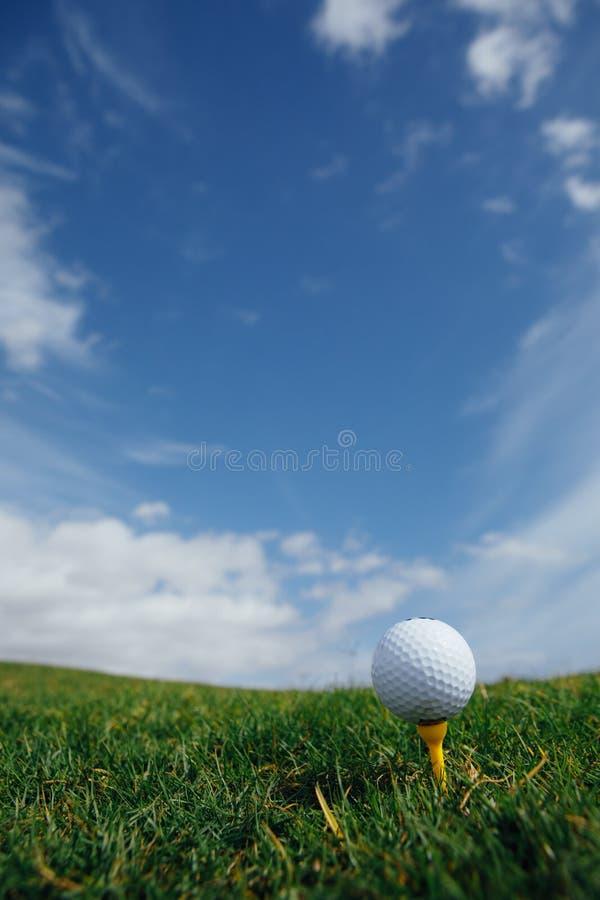 在发球区域、绿草和蓝天的高尔夫球 免版税库存照片
