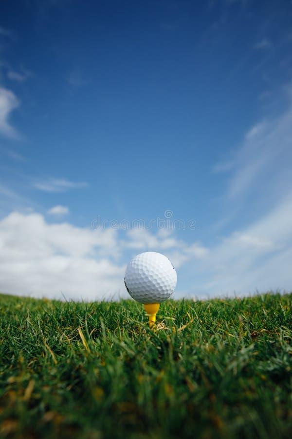 在发球区域、绿草和蓝天背景的高尔夫球 库存照片