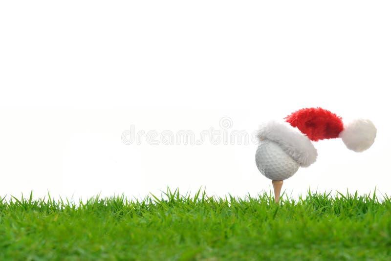 在发球区域的欢乐高尔夫球与圣诞老人项目的帽子 图库摄影