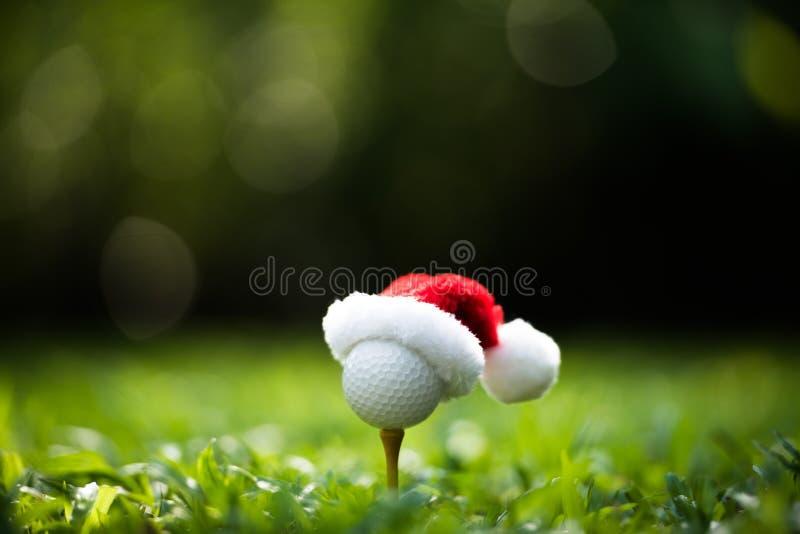 在发球区域的欢乐高尔夫球与圣诞老人项目的帽子 库存照片