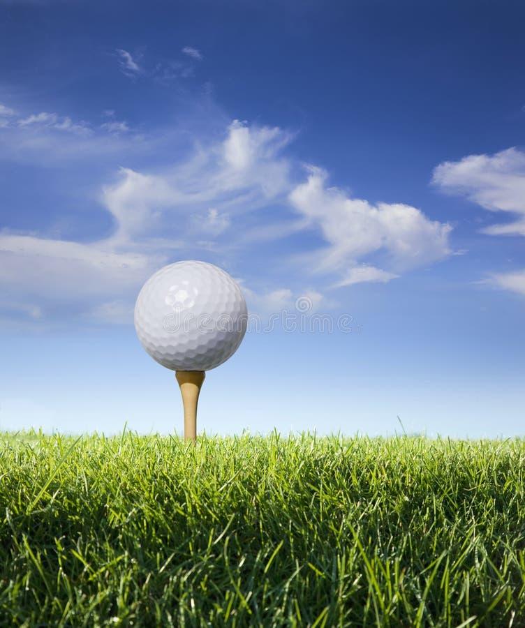 在发球区域的高尔夫球与草、蓝天和云彩 免版税库存照片