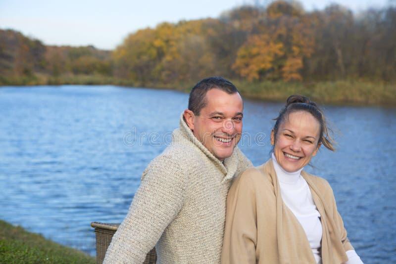 在变冷在秋天湖之前的爱的年轻夫妇 愉快的享受自然和拥抱的男人和妇女 免版税库存照片