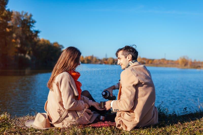 在变冷在秋天湖之前的爱的年轻夫妇 愉快的享用茶的男人和妇女户外 图库摄影