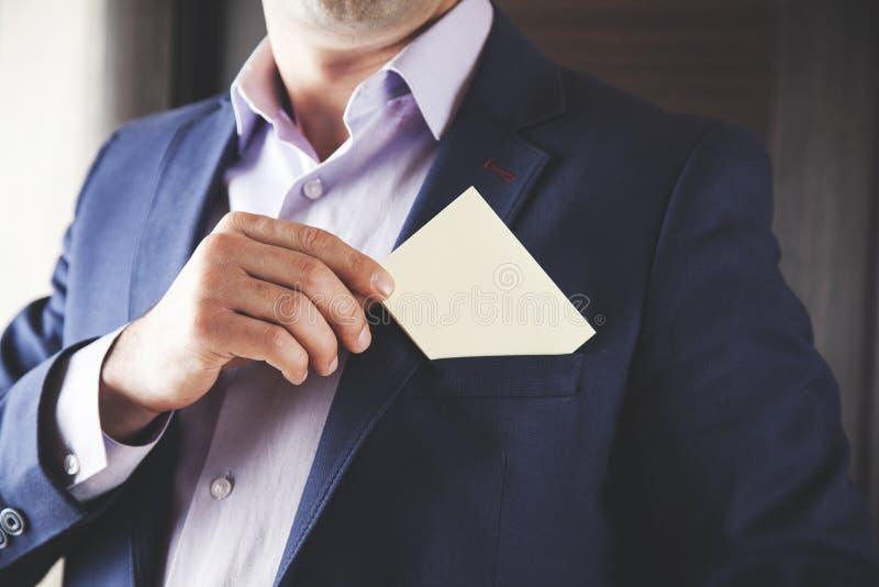 在口袋的商人陈列白色卡片 免版税图库摄影