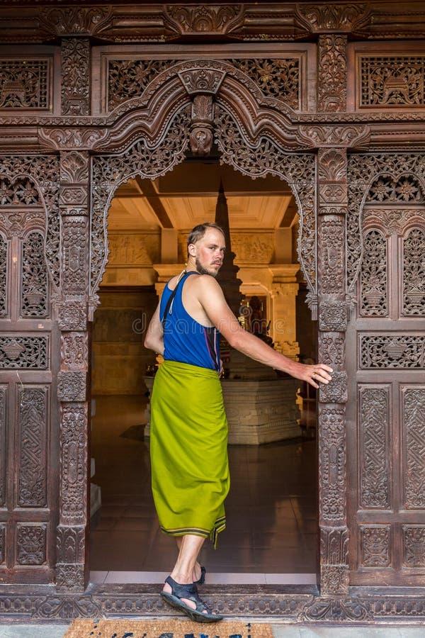 在古庙的木门的一个年轻人身分在乔德普尔城,印度 图库摄影